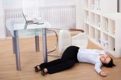 La femme d'affaires s'est évanouie sur le plancher photo stock