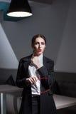 La femme d'affaires s'est habillée dans le costume et avec les lèvres et les verres rouges ; Photos stock