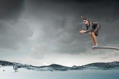 La femme d'affaires sautant dans l'eau Media mélangé Images stock