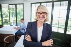La femme d'affaires se tenant avec des bras a croisé dans un restaurant Images libres de droits