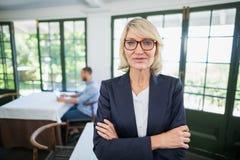 La femme d'affaires se tenant avec des bras a croisé dans un restaurant Photographie stock libre de droits