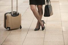 La femme d'affaires se tenant avec le voyage met en sac sur le trottoir de ville Images stock