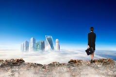 La femme d'affaires se tient au bord de la montagne et du regard sur la ville photo stock