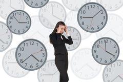 La femme d'affaires se tient parmi des horloges Photographie stock