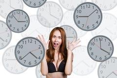 La femme d'affaires se tient parmi des horloges Photos libres de droits