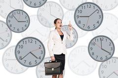 La femme d'affaires se tient parmi des horloges Images stock