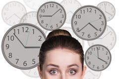La femme d'affaires se tient parmi des horloges Photo libre de droits