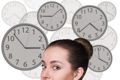 La femme d'affaires se tient parmi des horloges Image stock