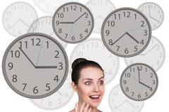 La femme d'affaires se tient parmi des horloges Image libre de droits