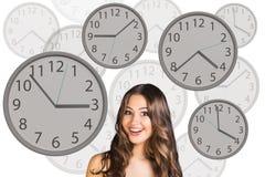 La femme d'affaires se tient parmi des horloges Images libres de droits