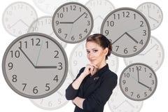 La femme d'affaires se tient parmi des horloges Photographie stock libre de droits