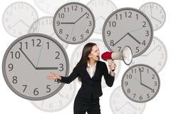 La femme d'affaires se tient parmi des horloges Photos stock