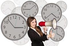 La femme d'affaires se tient parmi des horloges Photo stock