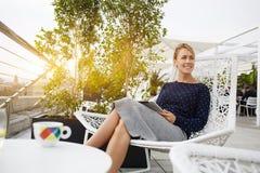 La femme d'affaires sourit pour quelqu'un, tandis que se repose avec le pavé tactile portatif dans le restaurant à l'air frais image libre de droits