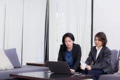 la femme d'affaires supérieure et junior discutent quelque chose pendant Photo stock