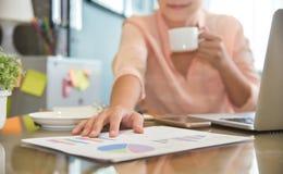 La femme d'affaires tenant dessus des graphiques et le graphique de gestion diagram le document images stock