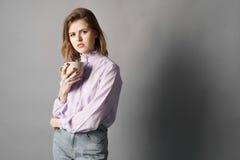 La femme d'affaires tient et tient une tasse dans sa main Brosse à dents Un sur un fond gris photo libre de droits