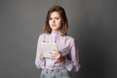 La femme d'affaires tient un carnet avec un stylo Quelque chose écrit et pense Brosse à dents Un sur un fond gris Photo libre de droits