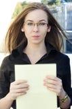 La femme d'affaires tient un dossier jaune avec le papier Photographie stock