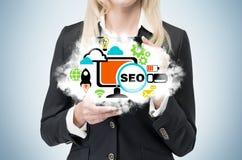 La femme d'affaires tient un nuage comme métaphore de 'SEO' Images stock