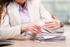 La femme d'affaires travaillant avec la pile de papiers Photos stock