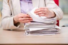 La femme d'affaires travaillant avec la pile de papiers Images libres de droits