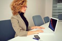 La femme d'affaires travaille avec l'ordinateur portable Photographie stock libre de droits