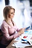 La femme d'affaires travaille avec les dispositifs modernes photographie stock
