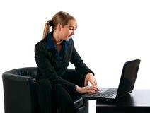 La femme d'affaires travaille derrière l'ordinateur portatif Image stock