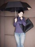 La femme d'affaires triste se trouve avec le parapluie et son sac à main sur le sofa Image libre de droits