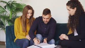 La femme d'affaires vend la maison aux ménages mariés, mari heureux signe l'accord d'achat et de vente, se serrant la main à banque de vidéos