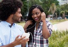 La femme d'afro-américain apprécie la musique avec l'ami de hippie Images stock