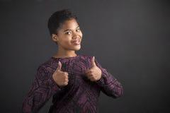 La femme d'afro-américain avec des pouces lèvent le signal de main sur le fond de tableau noir photo libre de droits