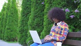 La femme d'afro-américain avec une coiffure Afro utilise un ordinateur portable se reposant sur le banc sur la rue MOIS lent banque de vidéos