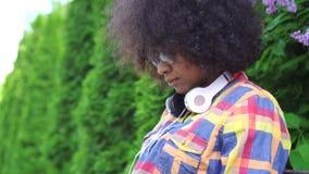 La femme d'afro-américain de portrait avec une coiffure Afro utilise un ordinateur portable se reposant sur le banc sur la rue MO banque de vidéos