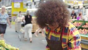 La femme d'afro-américain des employés de supermarché avec une coiffure Afro assortit la fin de fruit  banque de vidéos