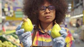 La femme d'afro-américain des employés de supermarché de portrait avec une coiffure Afro assortit le fruit banque de vidéos