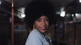La femme d'afro-américain regardant la caméra et la position de sourire dans le transport en commun, steadicam a tiré Plan rappro clips vidéos