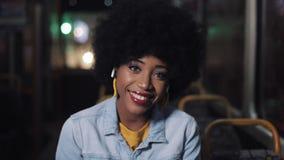 La femme d'afro-américain regardant la caméra et la séance de sourire dans le transport en commun, steadicam a tiré Plan rapproch clips vidéos