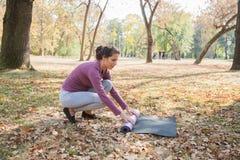 La femme d'ajustement se préparent au yoga Mat At Park de roulement d'exercice photos stock