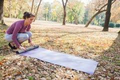 La femme d'ajustement se préparent au yoga Mat At Park de roulement d'exercice photos libres de droits