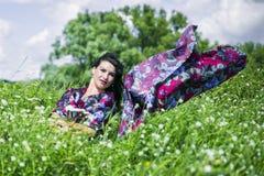 La femme d'amour de nature sur le gisement de fleur s'est habillée en tissu coloré Photographie stock