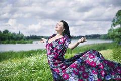 La femme d'amour de nature sur le gisement de fleur s'est habillée en tissu coloré Photographie stock libre de droits
