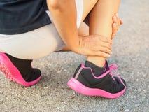 La femme d'athlète a la blessure à la cheville, jambe foulée pendant le trai courant photo stock