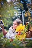 La femme d'automne heureuse en parc de chute s'étend au panier ayant l'amusement souriant dans le beau feuillage coloré de forêt Photo libre de droits