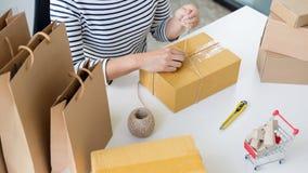 La femme d'entrepreneur travaillant des achats en ligne préparent le produit pac photo libre de droits