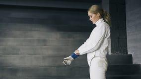 La femme d'escrimeur mettant sur les vêtements protecteurs et le casque se préparent à la concurrence de clôture à l'intérieur Image libre de droits