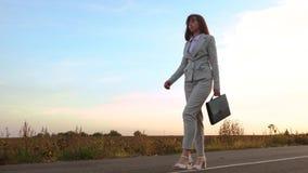 La femme d'homme d'affaires marche sur l'asphalte dans le pantalon et les chaussures à talons hauts blanches, porte une serviette banque de vidéos