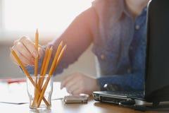 La femme d'indépendant prend un crayon au travail Photos stock