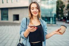 La femme d'intoxiqué de téléphone juge l'instrument et le café disponibles photographie stock